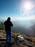 Высокорослый человек принимает фото камерой зеркала на шеи Пик Snowy скалистый горы Стоковые Изображения RF
