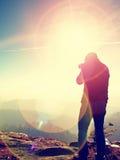 Высокорослый человек принимает фото камерой зеркала на шеи Пик Snowy скалистый горы Стоковое Изображение