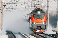 Высокоскоростной красный локомотивный пассажирский поезд едет на высокой скорости в зиме вокруг снежного ландшафта Стоковые Изображения