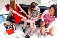 Высоко-угол снял усмехаясь подруг выбирая установку на ботинки спорт сидя на стенде беседуя и смеясь над пока Стоковое фото RF