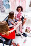 Высоко-угол снял усмехаясь подруг выбирая установку на ботинки спорт сидя на стенде беседуя и смеясь над пока Стоковые Изображения