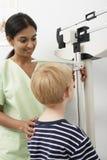 Высота измеряя мальчика медсестры стоковое изображение rf