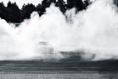 Выставка автомобиля смещения на автосалоне Бухареста Перемещаться колеса спортивной машины, окруженный дымом стоковая фотография rf