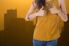 Выставка бизнес-леди thumbs вверх с городом в предпосылке стоковая фотография