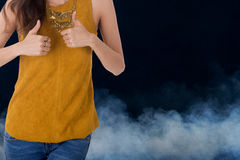 Выставка бизнес-леди thumbs вверх с дымом в предпосылке стоковое изображение
