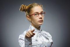 Выставка крупного плана заботливая или презрительная девушки на камере изолированной на сером цвете Стоковые Изображения RF