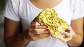 Выставка руки женщины есть футболку белизны здравицы сыра хлеба авокадоа Стоковое фото RF