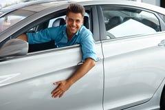 Выставочный зал автомобиля Счастливый человек внутри автомобиля его мечты Стоковые Изображения RF