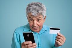 Выстрел в голову зрелого человека с серыми волосами держит мобильный телефон и кредитная карточка, делает оплату онлайн, одетый в стоковая фотография rf