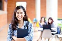 Выстрел в голову молодого счастливого привлекательного азиатского студента усмехаясь и смотря камеру с друзьями на на открытом во стоковые изображения