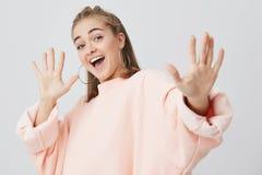Выстрел в голову привлекательный усмехаться при открытый рот демонстрируя ее длинн-sleeved женщину белых зубов молодую одел в пин стоковая фотография rf
