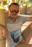 Выстрел в голову кавказского человека в его последних двадчадках с солнечными очками авиатора дизайнерской стерни нося Outdoors,  Стоковые Фото