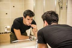 Выстрел в голову привлекательных зубов молодого человека чистя щеткой Стоковые Изображения