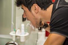 Выстрел в голову привлекательных зубов молодого человека чистя щеткой Стоковые Изображения RF