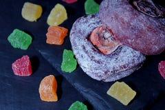 Высушенная хурма с лож напудренного сахара на каменном блюде, на темной предпосылке Рядом разбросанные пестротканые части candied стоковая фотография