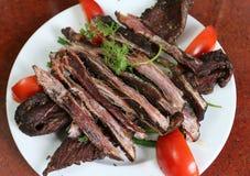 Высушенное мясо буйвола на белом блюде с томатом и травами Стоковое Изображение