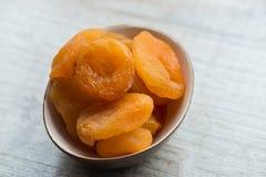 Высушенные абрикосы в коричневой плите на белой предпосылке Конец-вверх Стоковая Фотография RF