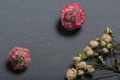 Высушенные бежевые розы На фоне текстуры серой ткани грубой Рядом 2 декоративных шарика высушенной травы  стоковое фото rf