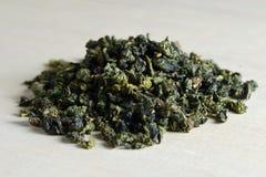 Высушенные листья зеленого чая на предпосылке деревянной доски Стоковая Фотография