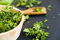 Высушенные листья cilantro на деревянной ложке Естественный свет Селективный фокус Закройте вверх на черной предпосылке Взгляд св Стоковая Фотография RF