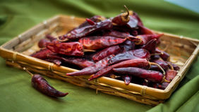 Высушенные накаленные докрасна перцы chili лежат в куче, glitering с различными тенями красного цвета Стоковое Изображение