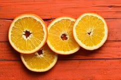 Высушенные оранжевые куски на оранжевой деревянной предпосылке Взгляд сверху Стоковое фото RF