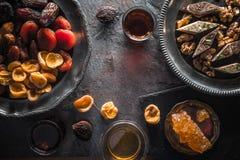 Высушенные плодоовощи, гайки на плите и чай на сером конце-вверх шифера Стоковое Изображение