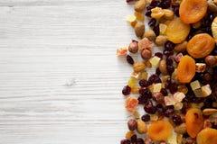 Высушенные плоды и смешивание на белой деревянной предпосылке, взгляд сверху гайки r   стоковые изображения