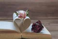 Высушенные розы с кольцом с бриллиантом на деревянном годе сбора винограда предпосылки тонизируют стоковые фотографии rf
