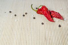 2 высушили накаленный докрасна перец, соль моря и черные перчинки на бамбуковом serviette стоковая фотография