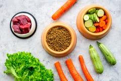 Высушите органический корм для домашних животных с свежими овощами и мясом в пластичном шаре для подавая собак на каменном взгляд Стоковые Фото