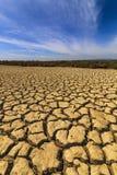 Высушите треснутую землю под голубым небом Стоковое фото RF