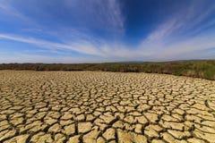Высушите треснутую землю под голубым небом Стоковое Фото