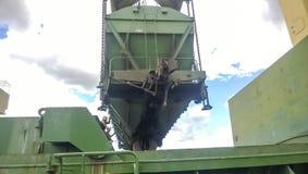 Высыпание зерна от автомобиля в владение топливозаправщика Завалка зерна грузового помещения корабля Стоковое Изображение