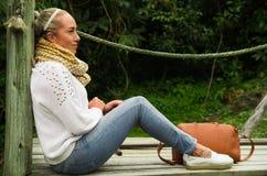 Вытаращиться красивой молодой созерцательной женщины сидя на природе Стоковое Фото
