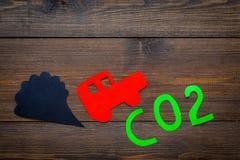 Вытыхание автомобиля, СО2, дым Автомобиль и вырез дыма на темном деревянном взгляд сверху предпосылки копируют космос Стоковые Изображения RF