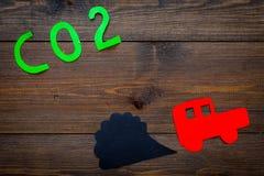 Вытыхание автомобиля, СО2, дым Автомобиль и вырез дыма на темном деревянном взгляд сверху предпосылки копируют космос Стоковые Фото