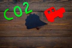 Вытыхание автомобиля, СО2, дым Автомобиль и вырез дыма на темном деревянном взгляд сверху предпосылки копируют космос Стоковое фото RF
