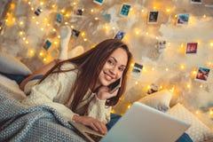 Выходные молодой женщины дома украсили спальню говоря smartphone Стоковые Изображения RF