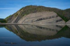 Выход на поверхность наслоенных утесов в крутом банке реки Стоковое Изображение RF