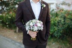 Выхольте в коричневом костюме с красивым букетом белых и пурпурных роз Ожидание невесты на улице Белая рубашка стоковые фото