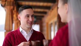 Выхольте и кофе напитка невесты или чай из чашек на балконе деревянного коттеджа шале журнала в деревне и поцелуя со снегом видеоматериал