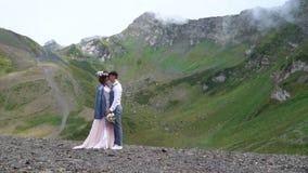 Выхольте и положение невесты во фронте далеких дивных зеленых горных пиков Великолепная свадьба outdoors акции видеоматериалы