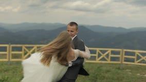 Выхольте невесту владениями в его оружиях на холмах горы r E акции видеоматериалы