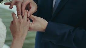 Выхольте носит обручальное кольцо на пальце невесты Свадебная церемония около воды Руки замужества с кольцами близко сток-видео