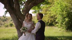 Выхольте приходит к очаровывать белокурую невесту с букетом за ей ( сток-видео