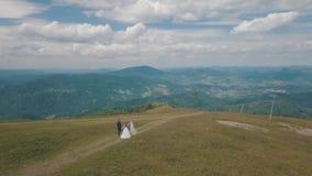 Выхольте с невестой идя совместно на холмы горы Воздушная съемка трутня сток-видео