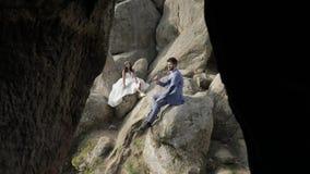 Выхольте с невестой сидите на высоком наклоне горы ювелирные изделия cravat пар кристаллические связывают венчание Счастливый сток-видео