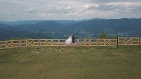Выхольте с невестой сидите на загородке около холмов горы Воздушная съемка трутня видеоматериал