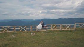 Выхольте с невестой сидите на загородке около холмов горы Воздушная съемка трутня акции видеоматериалы